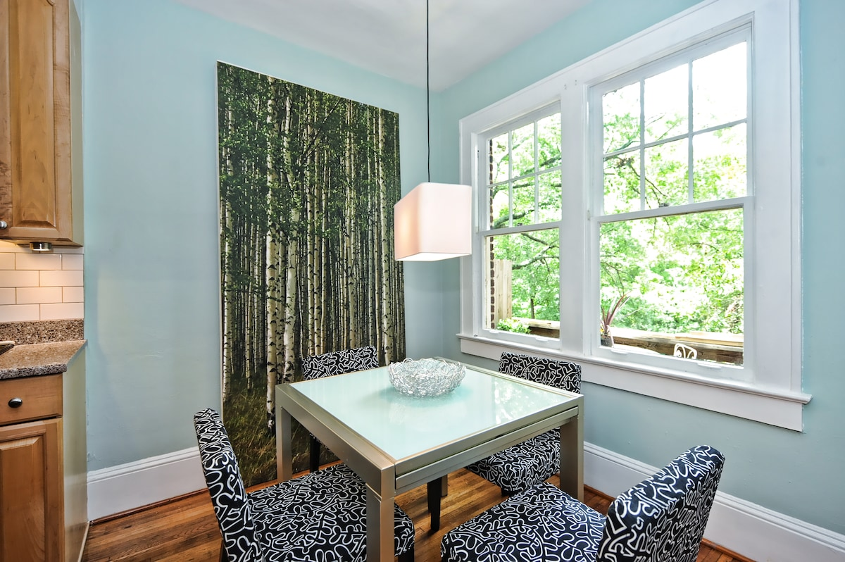 The bright and sunny dining area features a gorgeous view through the trees, and the table extends to seat 6.