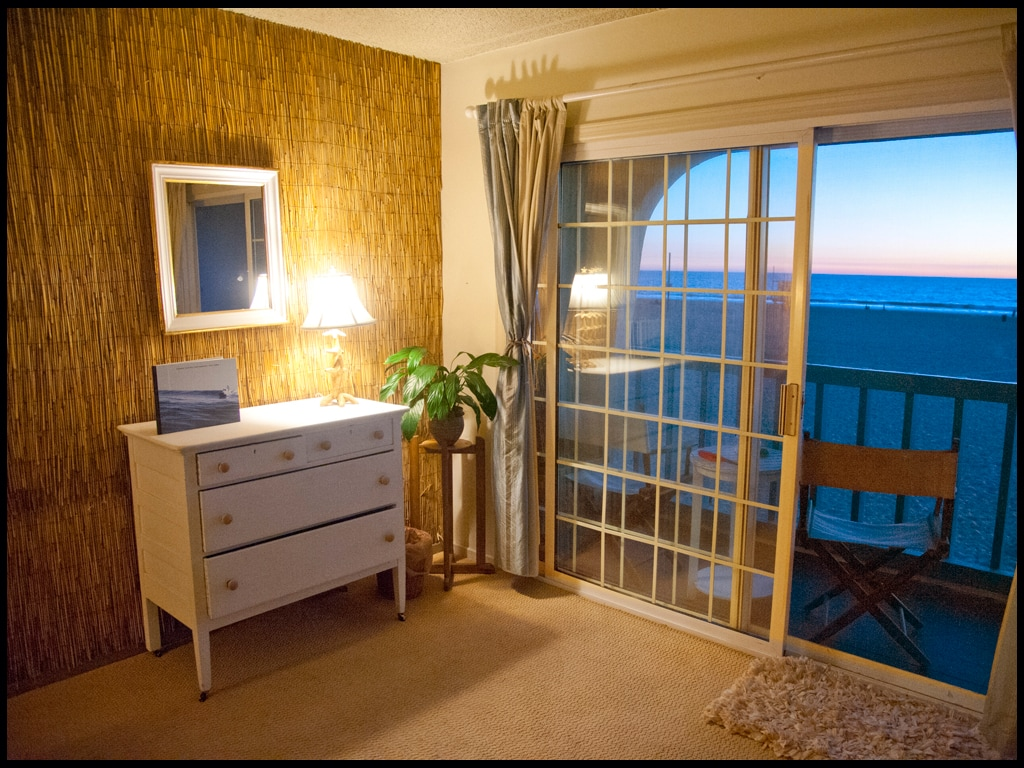 Tropical bamboo decor, dresser, vintage surf books and your own private balcony overlooking the ocean front at sunset.