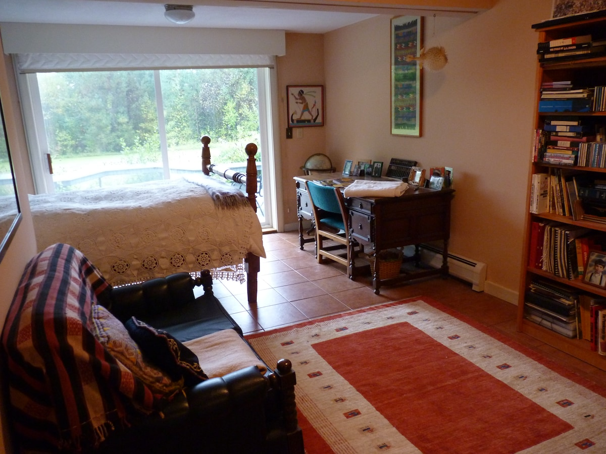 The room has a double bed, desk, couch, and a small cooking area.