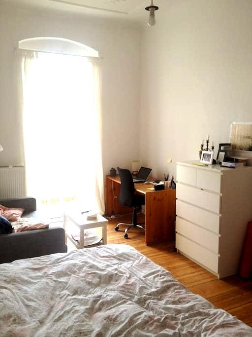 Bright airy room with large bed, balcony, and sofa - Berlín