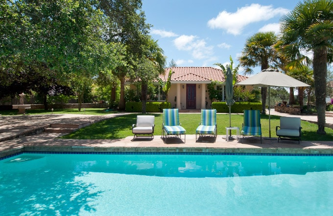 The 1000 square foot guest cottage enjoys easy access to the sparkling pool. Red tiles against bright blue skies and palm trees bending toward the lush lawns transport you to the tropics.