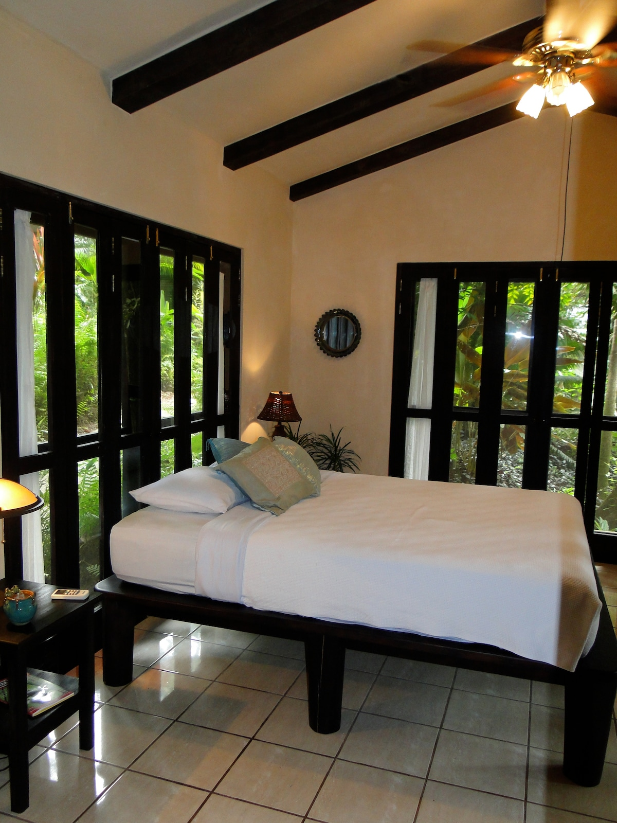 guest bedroom with orth. queen bed and 100% high count cotton sheets,   all doors fold back with screens in place for the experience of open air and the sounds of the jungle.