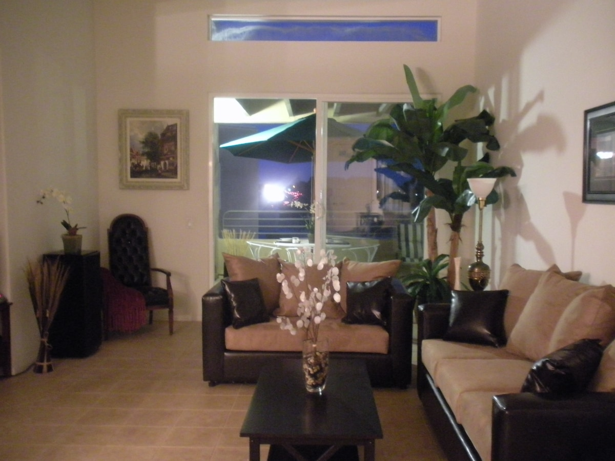 Large spacious living room with high ceilings with ceiling fan! Designer leather furniture.