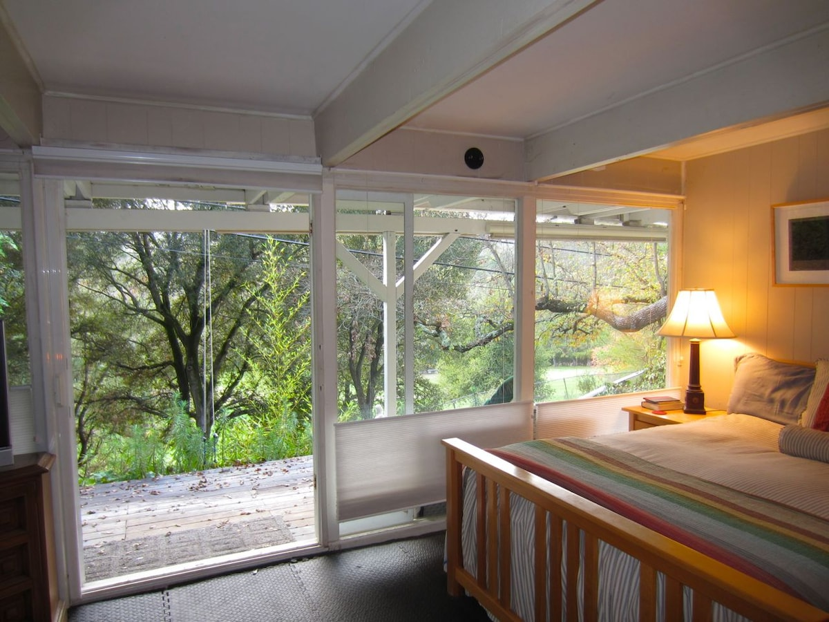 The queen size bed looks out through mature oaks onto the golf course