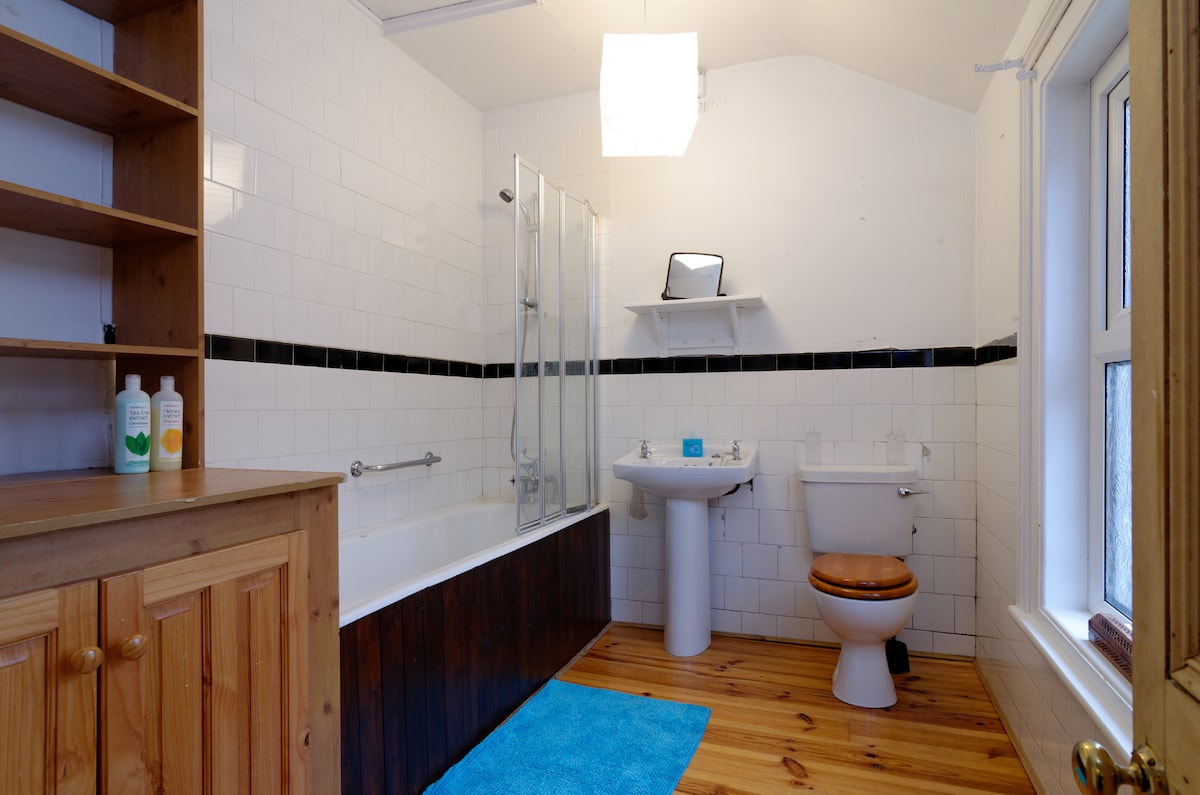 spacious light bathroom, with instant hot water, shower and bath, clean towels provided