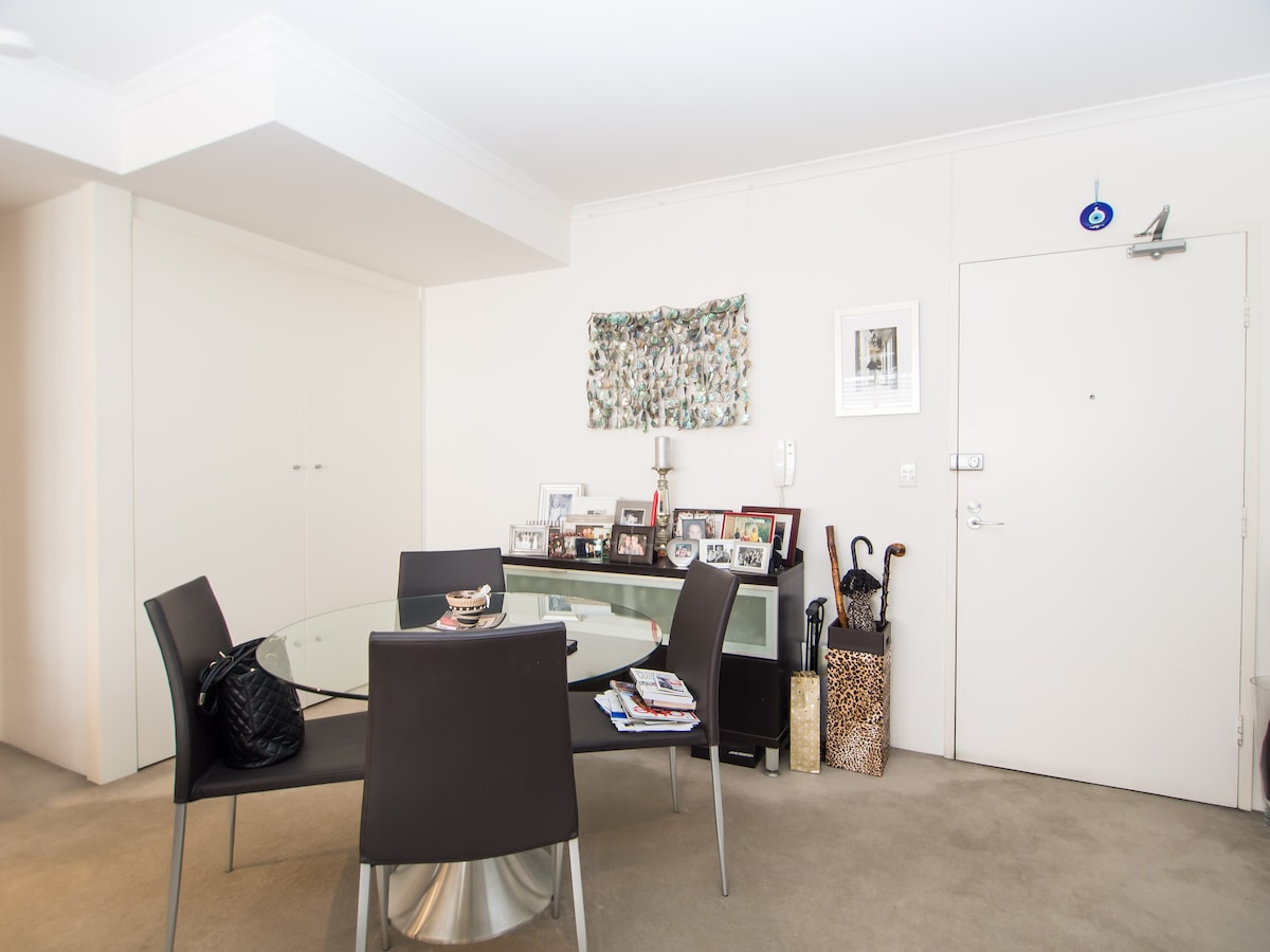 Dining table with full laundry behind white doors