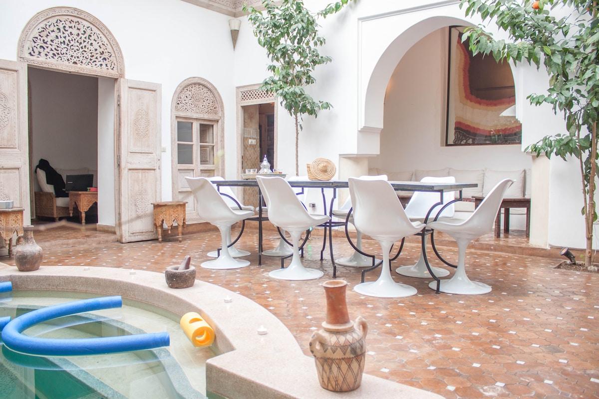 Vue du patio avec l'entrée vers le salon, le coin repas et le b'hou (salon en alcove ouvert sur le patio)