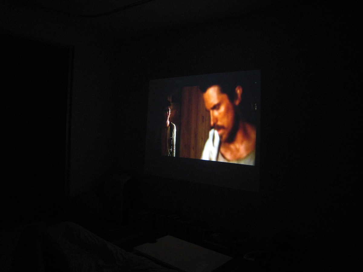 Movie projected on the wall facing the bed.