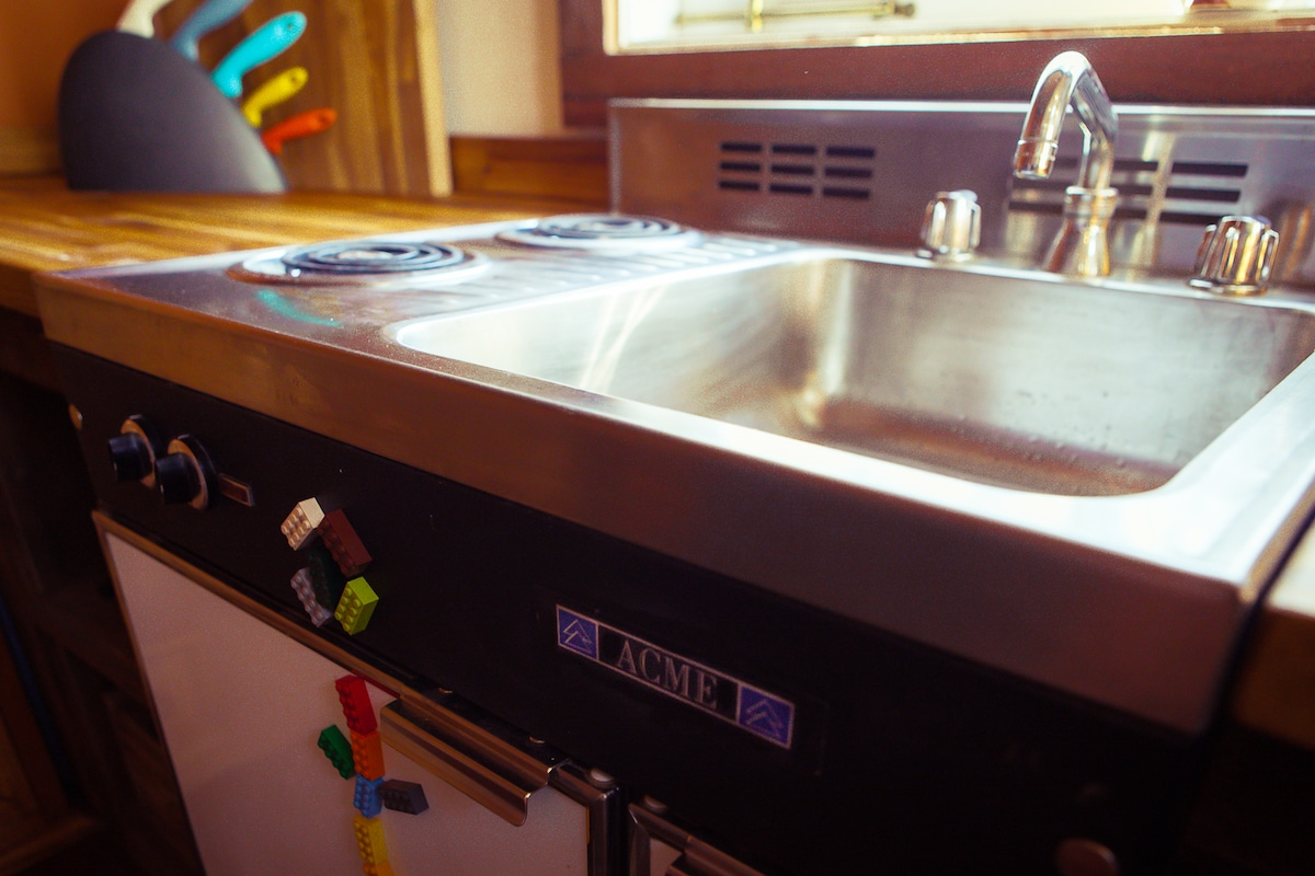 The ACME kitchenette boasts a two-burner stove, sink, and below, the refrigerator and freezer. Perfect for a short-stay. This is a vintage item, however amazingly ACME is still in business today making these tiny units.