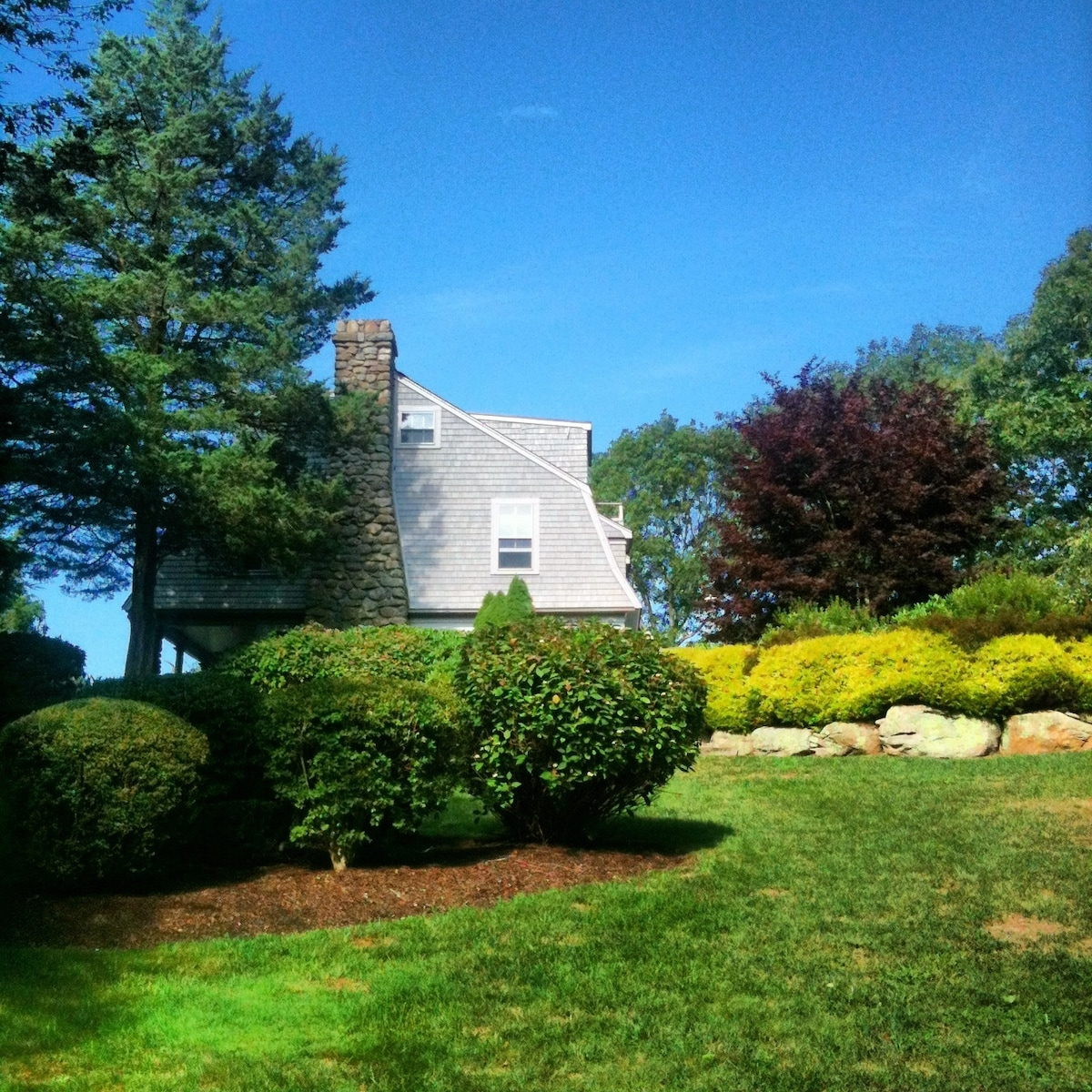 View of Pond House from down near the dock. It was built in the early 1900s, in the cottage-style popularized by the firm McKim, Mead, and White—fieldstone fireplace, wainscot for all the walls, and a terrace for reading, grilling, viewing the water....