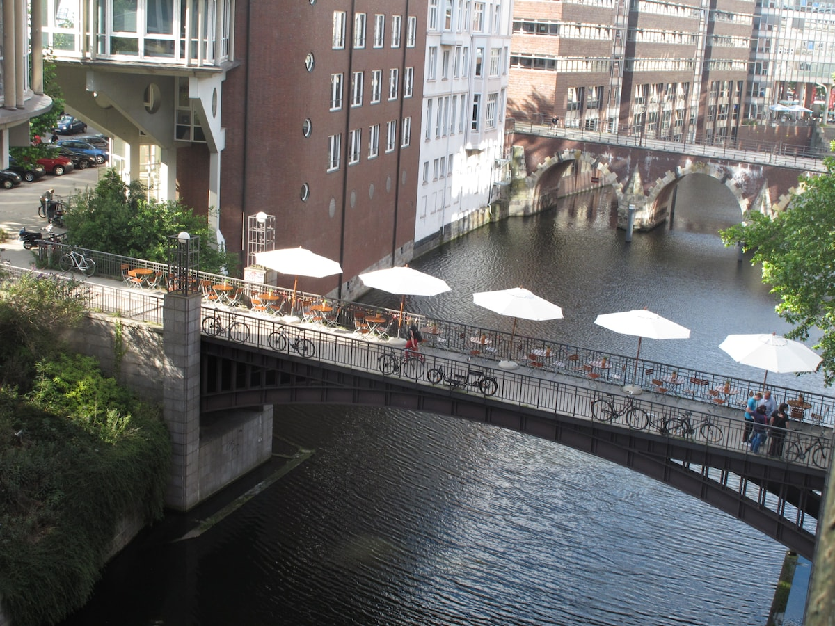 A view from the window down onto the canal, with the tables and parasols of the Rialto restaurant.