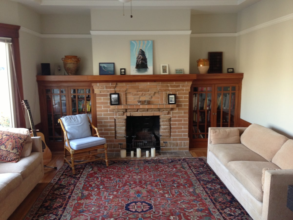Open living room with plush couches, decorative fire place, bay windows, flat screen tv and record player