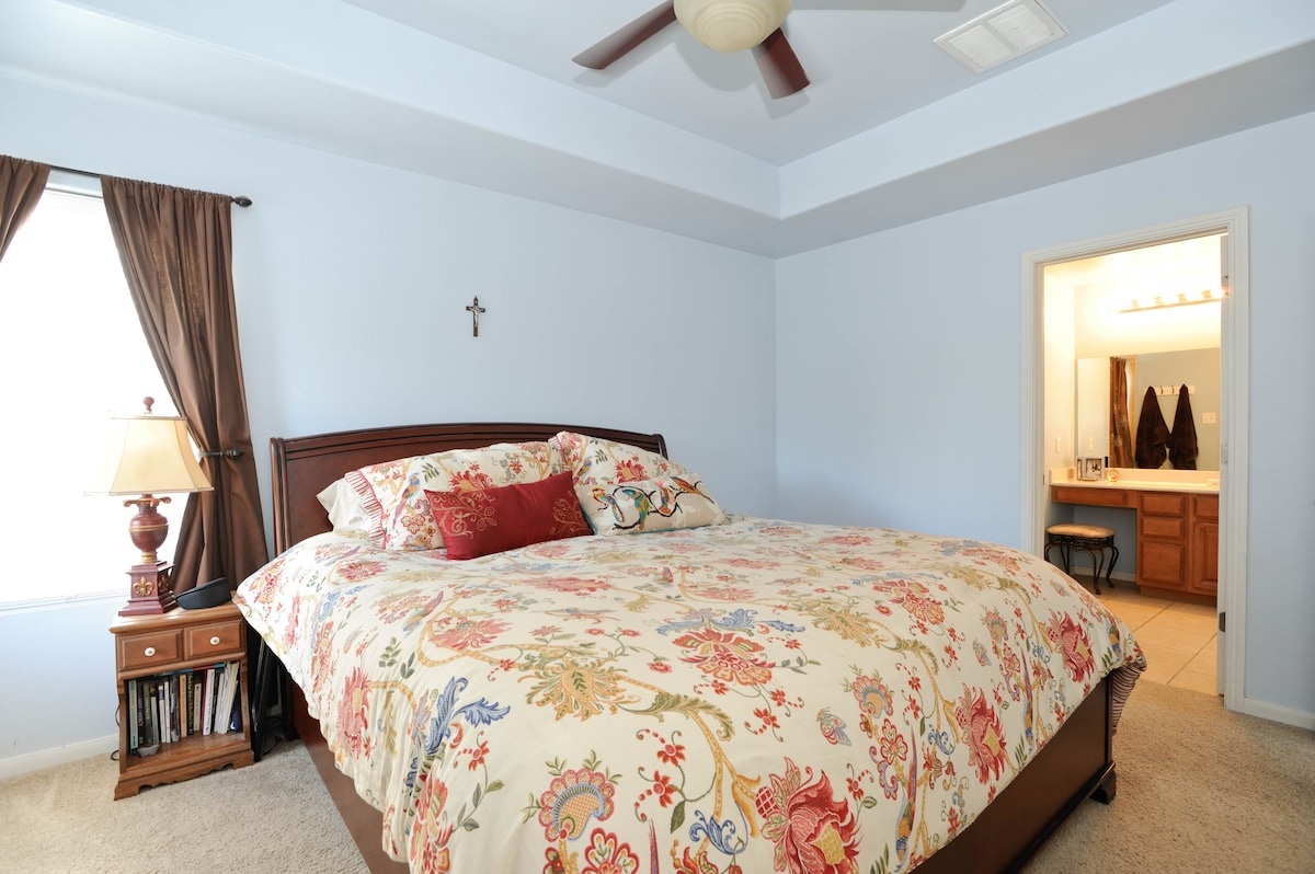 Master bedroom with a king sized bed and private bath