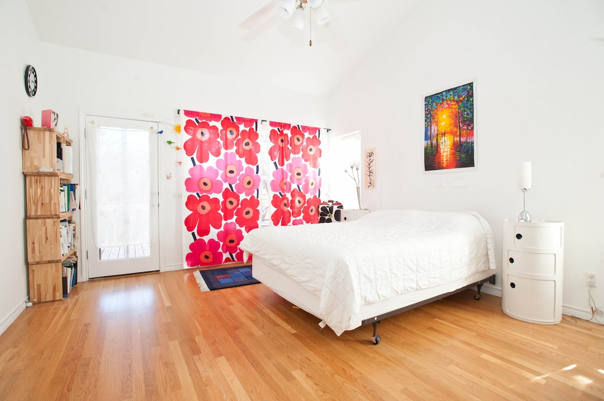Master bedroom with door leading to deck and glider swing.