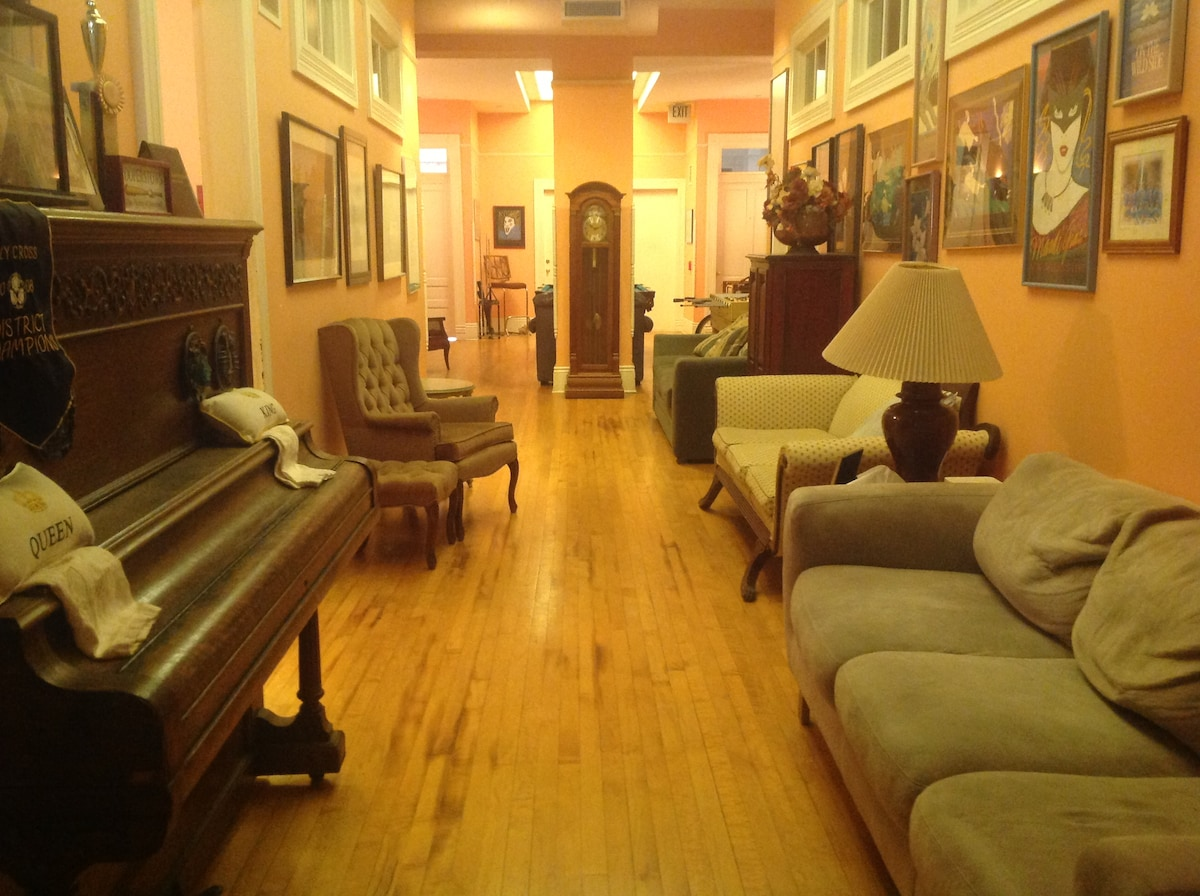 Hallway to apartment behind piano.  Pool table, games, laundry past Grandfather clock.