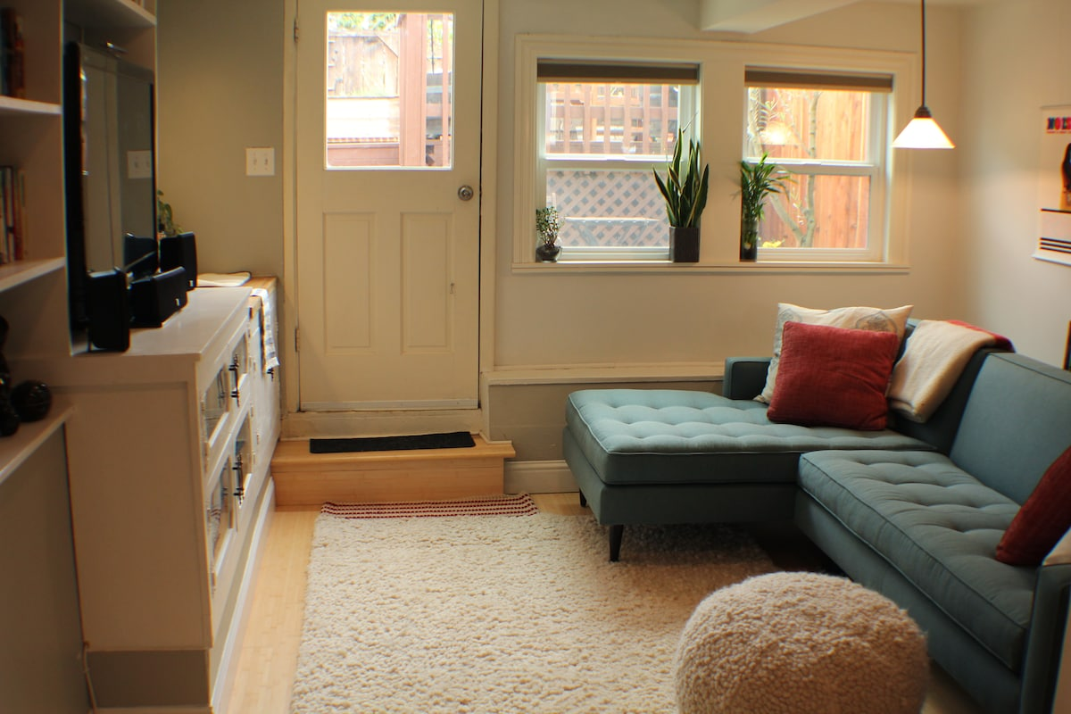 """The bonus room or """"chill room,"""" a cozy place to hang. Kitchenette and entertainment center on the left, door to backyard and patio straight ahead."""