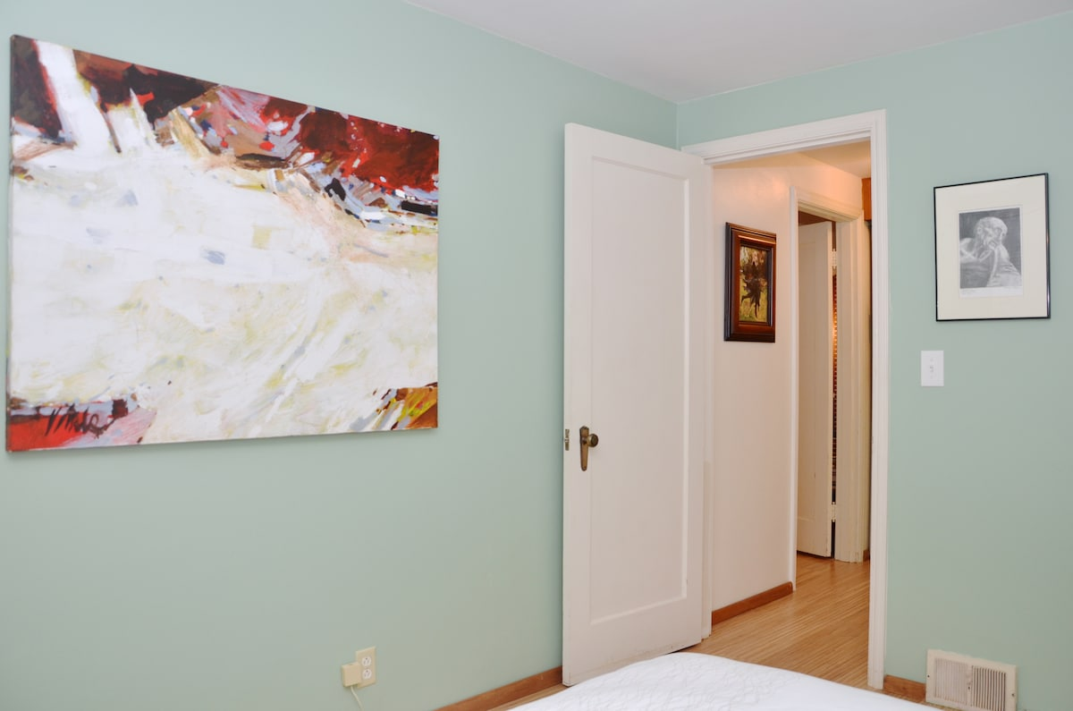 Beautiful room with a queen bed, wood floors and original art!