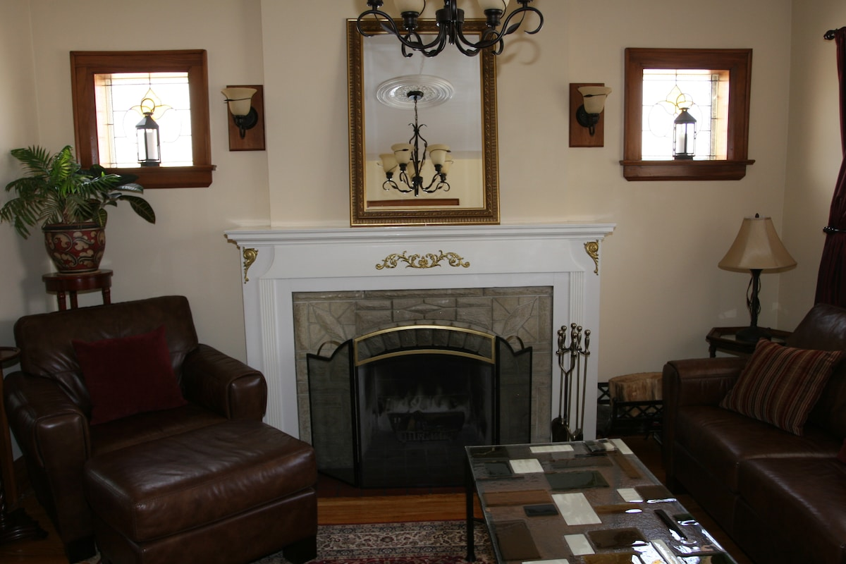 Living room with stained glass windows, French doors and wood burning fireplace