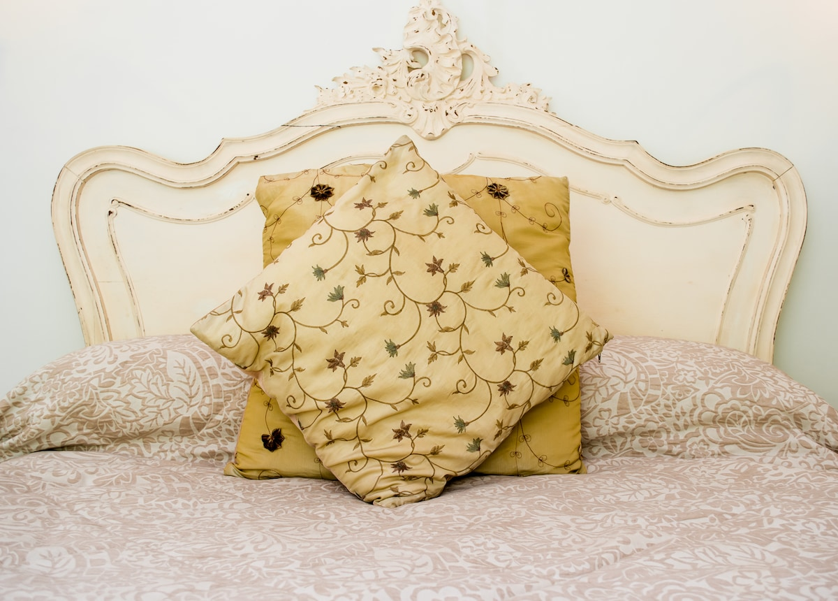 A close-up view of the silk cushions and Dormer bedding at the bedhead of this antique bed. Notice the intricate ornate rococo handcarving on the finial.