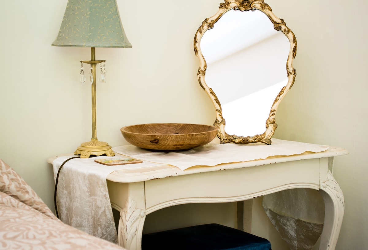 A vintage mirror sits on the pretty dressing table in The Dalesway. A lamp with cyrstal drops lends elegance to the room.