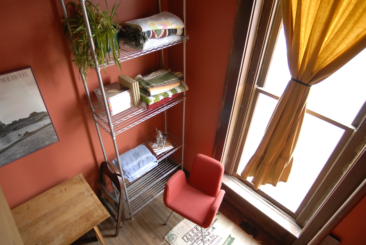 Writing desk, reading chair and large window facing downtown.