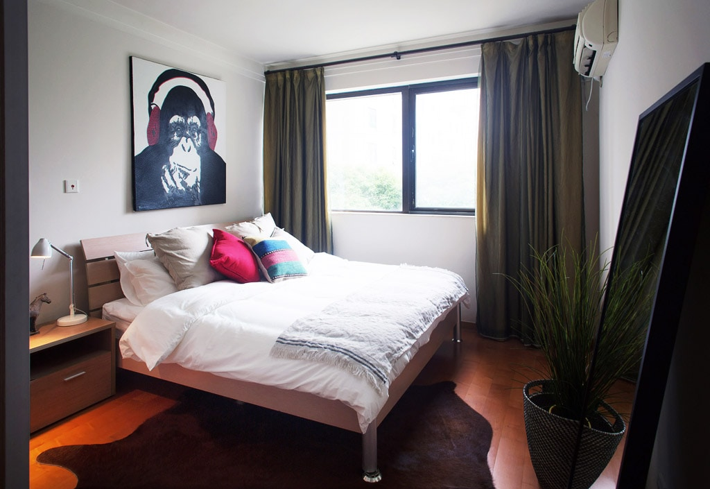 Master bedroom with luxury bedding and blackout curtains for peaceful sleep.