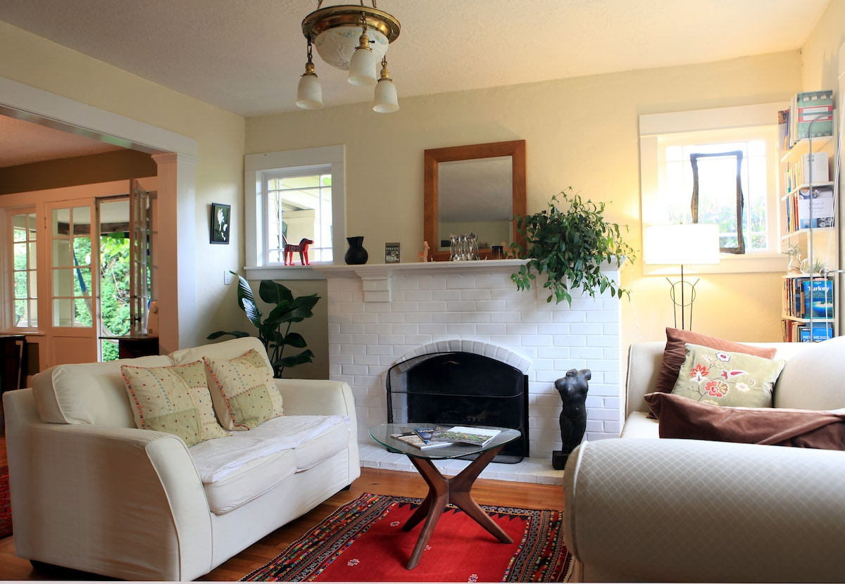Living room with a big window and fire place to relax.
