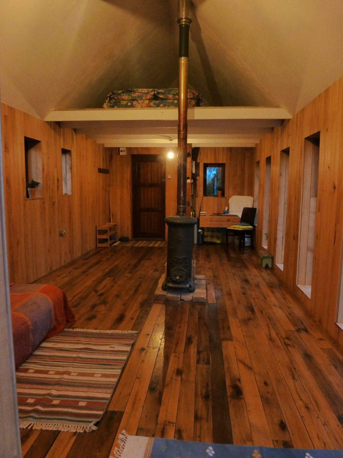 Badgers Hill Chalet, warm and relaxing. Above, the sleeping loft, with a double mattress. Ground floor, futon sofa that open into double bed.