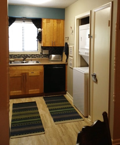 The compact washer/drier is located in the kitchen.