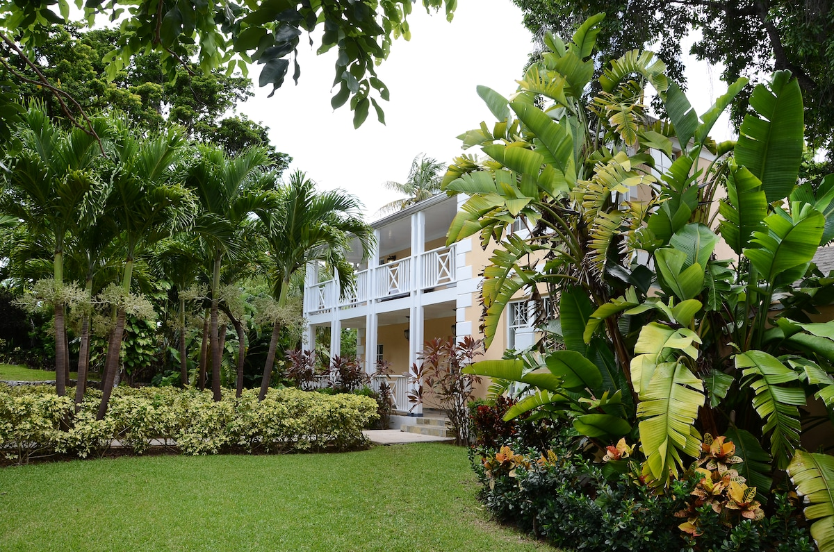 Beautifully landscaped gardens surround the elegant colonial home.