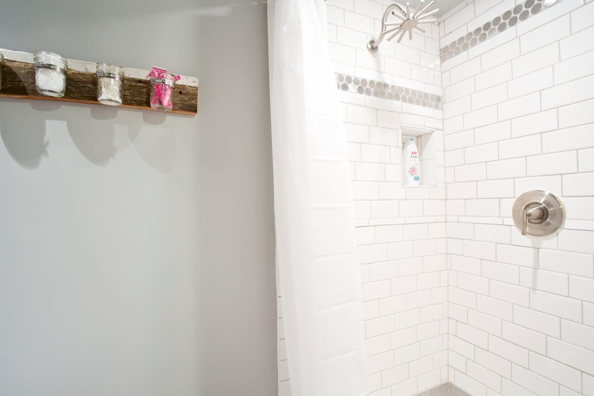 Custom-built bathroom with toiletries, shipwheel-style showerhead and subway tiling.