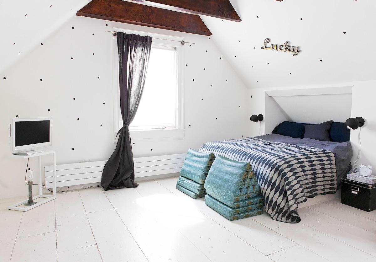 Attic bedroom on top floor. Exposed wood beams, white floors  polka dots!