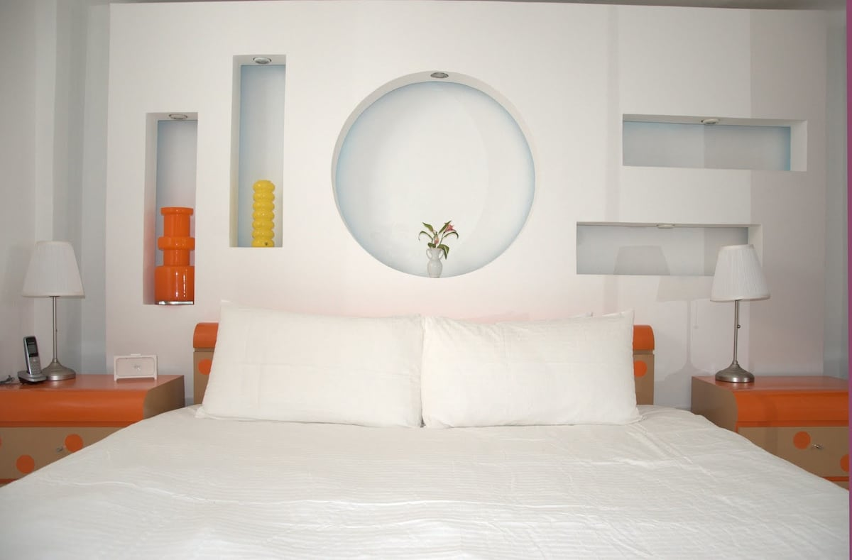 KING bed, art deco wall with colored lights in back of bed in 2 bedroom suite