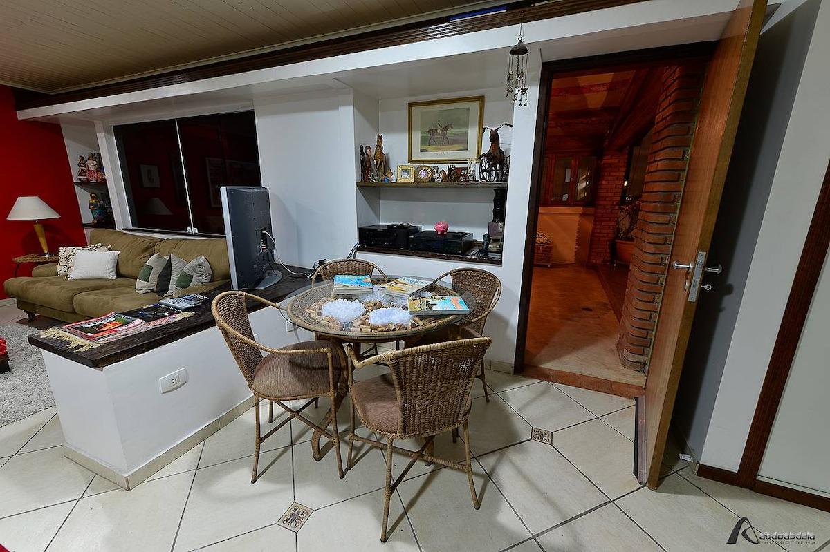 Vista lateral da área interna, mesa 4 cadeiras, som e acesso à área externa // Side view of the indoor area, table 4 chairs, sound and access to the outdoor area