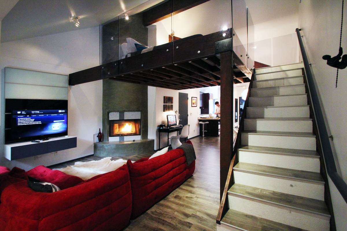 """Open living space with a """"floating bedroom"""" situated on a loft mezzanine."""