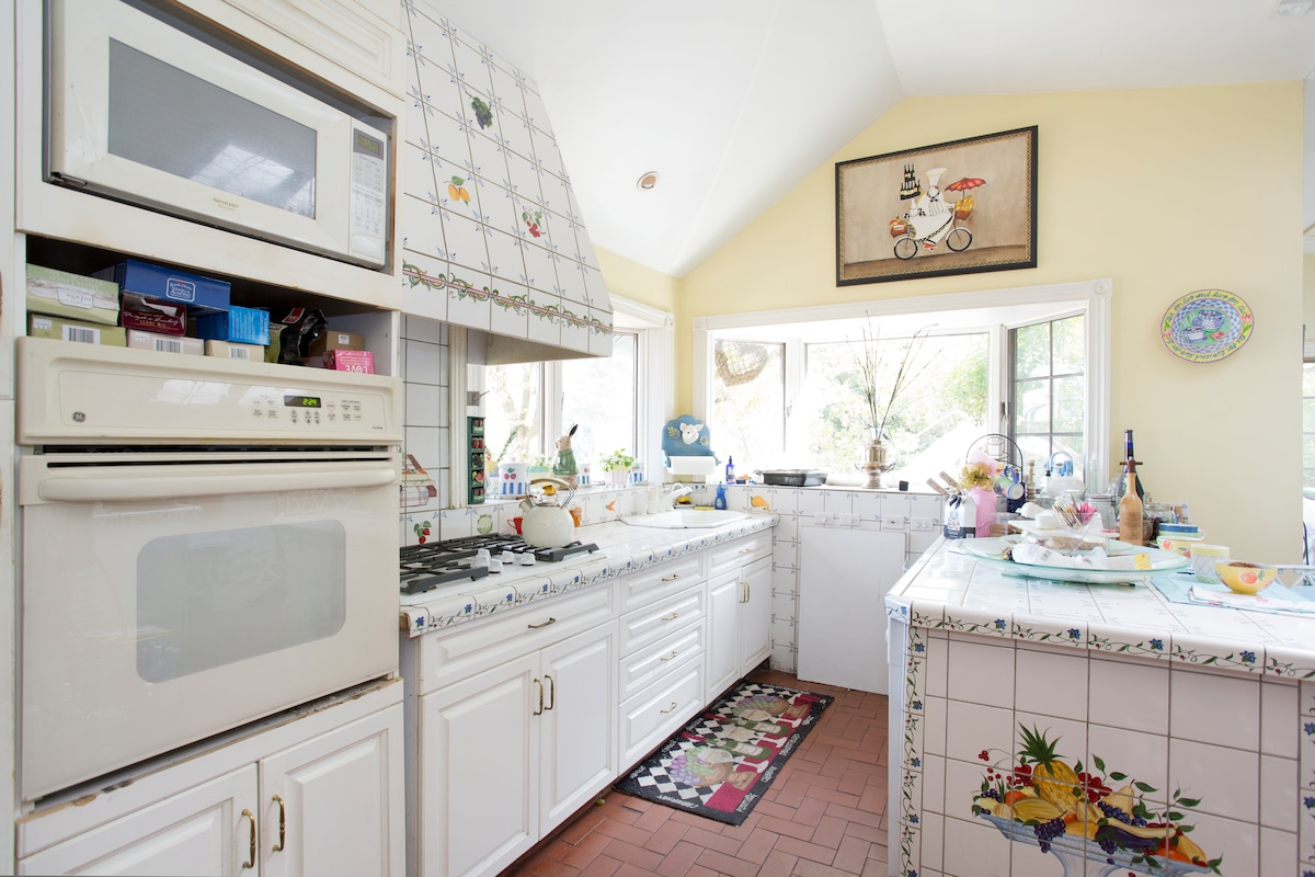 Italian tiled kitchen with gas stove, overlooking the garden and the bay