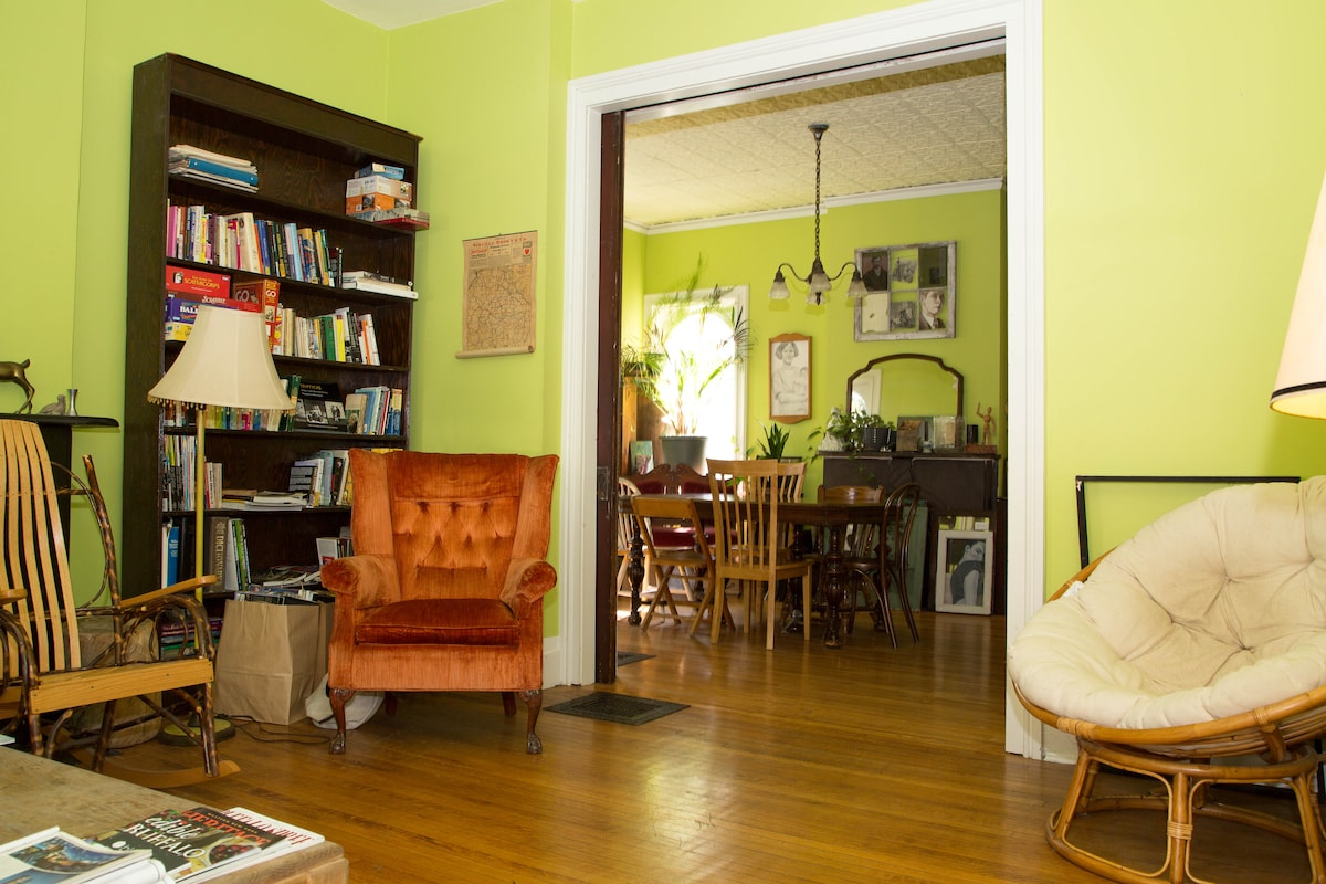 The living room/parlor with pocket doors features plenty of books, magazines, and a gas fireplace!