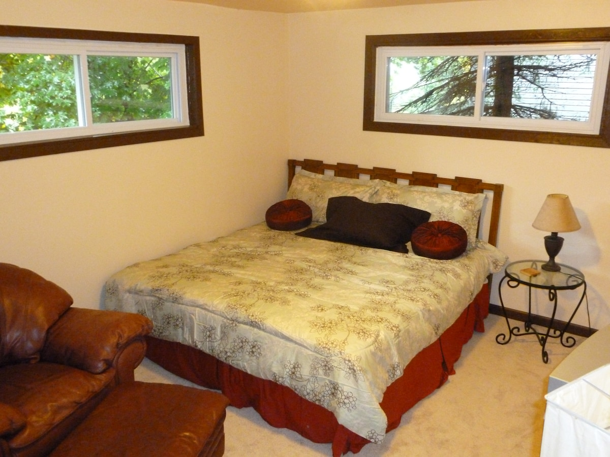 Master Bedroom with a King Sized Bed, Lounge chair, ottoman, HDTV television and DVD player.