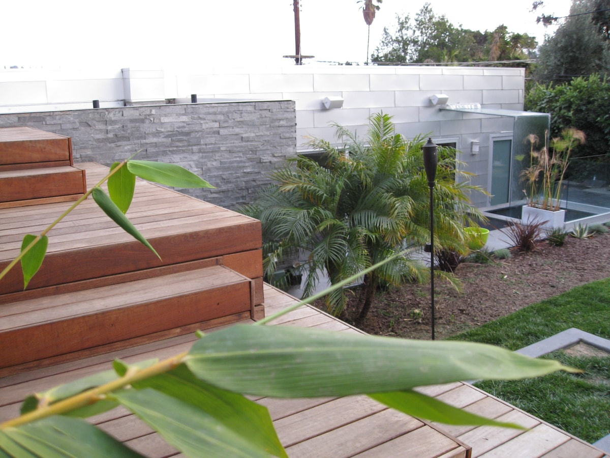 Large shared back garden and decks separate the main house from the guest house
