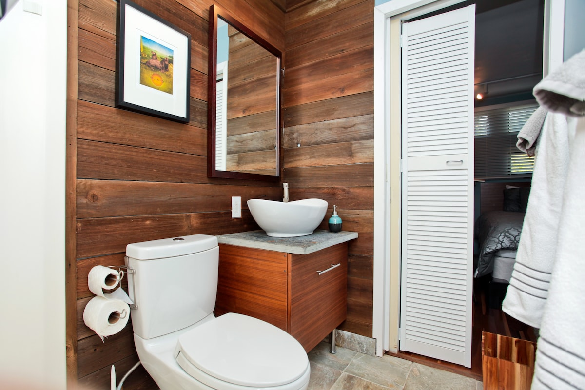 Don't let the reclaimed wood wall fool you: our bathroom has modern conveniences like a dual flush toilet, hairdryer and shampoo/body wash.