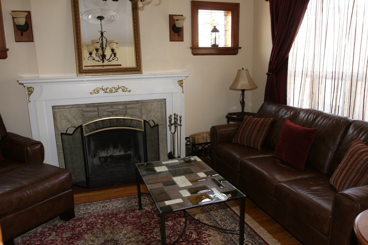 Living room with leather couch & chairs, stereo, fireplace