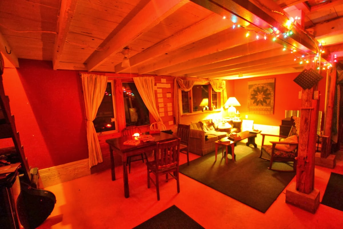 The Cozy Cottage - main floor - living room with Wood Stove on right and dining area on left