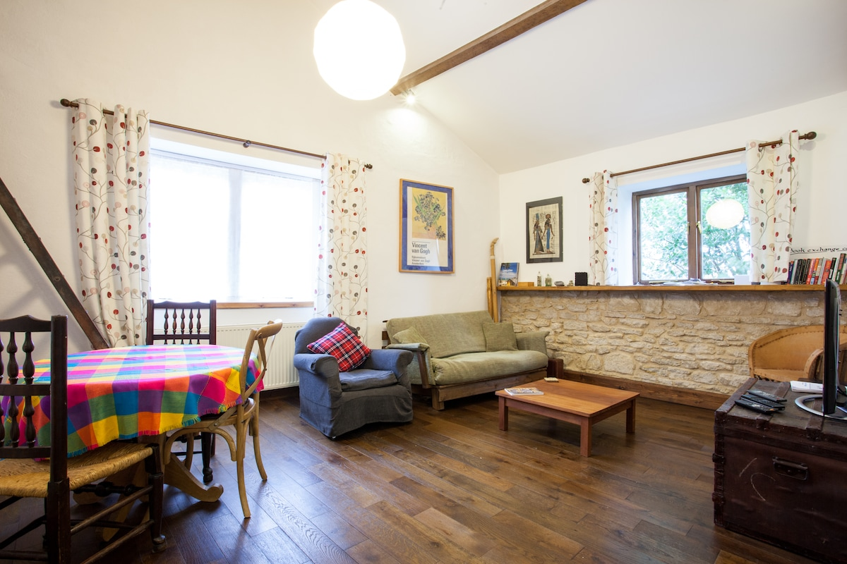 Dining area & lounge with comfy futon, armchair and original stone wall, TV