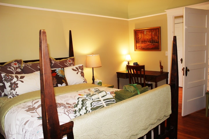 The Muir Woods room is the second room on the right. It has a rough hewn wood 4-poster queen bed that's extra long, an antique desk, end tables, and a futon chair to sleep a 3rd person.