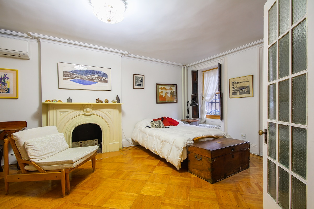 The front bedroom sleeps one, two or three. It is large and bright, with storage closets, a dresser, TV and a desk.
