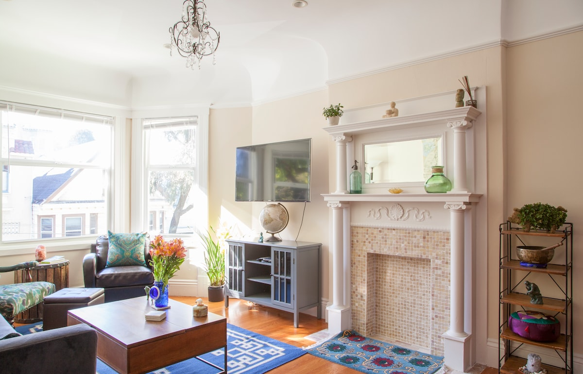 Main living room in top unit 3 bedroom/2 bath space. Tiled fireplace and beautiful original hardwood floors from 1908 construction of house.