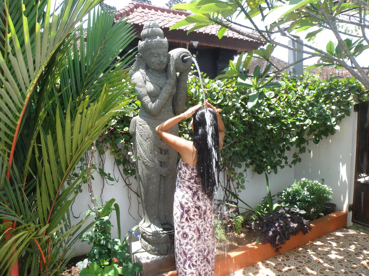 Dewi Sri , the Goddess of rice and prosperity blesses with a refreshing shower in the sunny Bali day