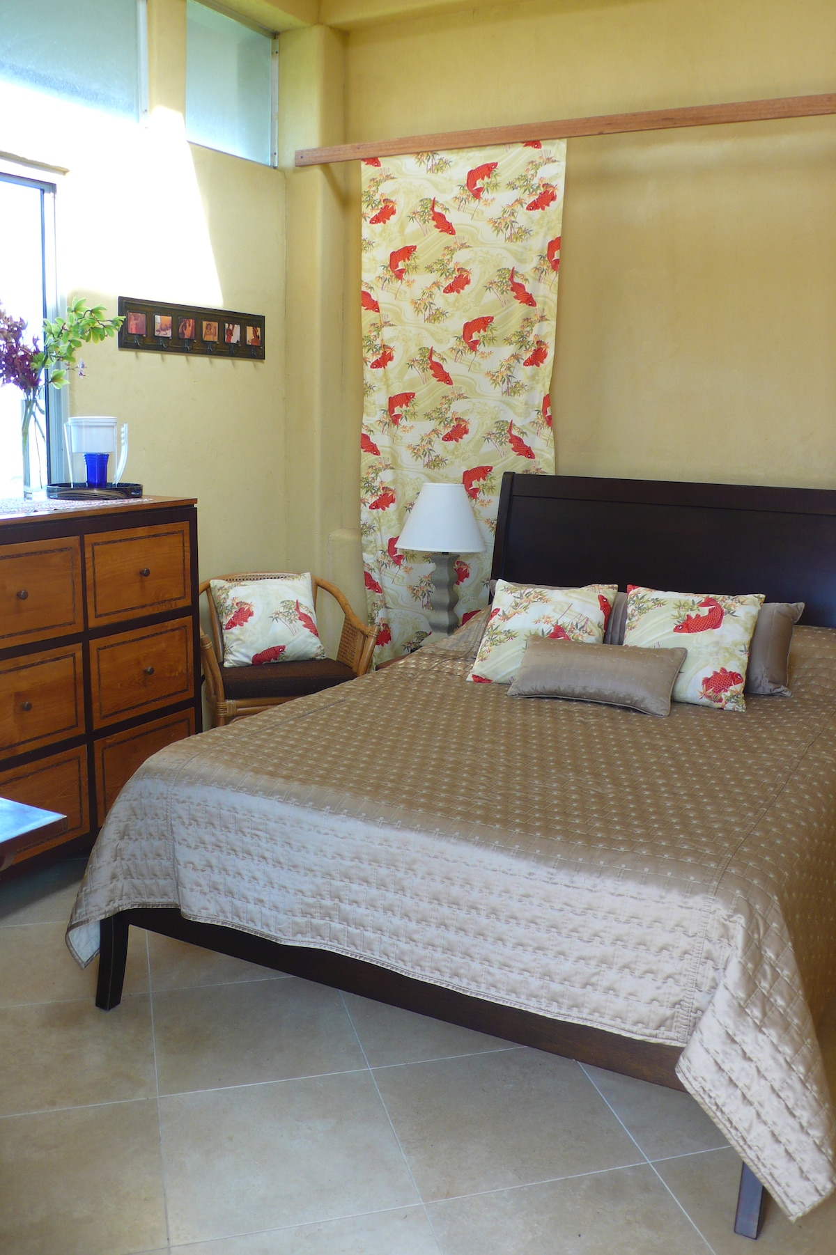 Partial view of guestroom with tropical hardwood dresser