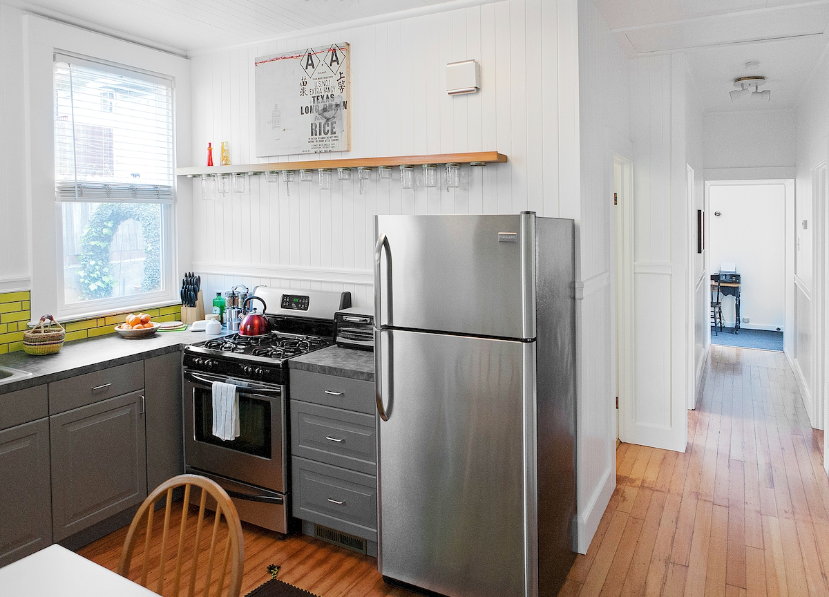 Spacious kitchen with new cabinets, dishwasher, refrigerator, counters and sink