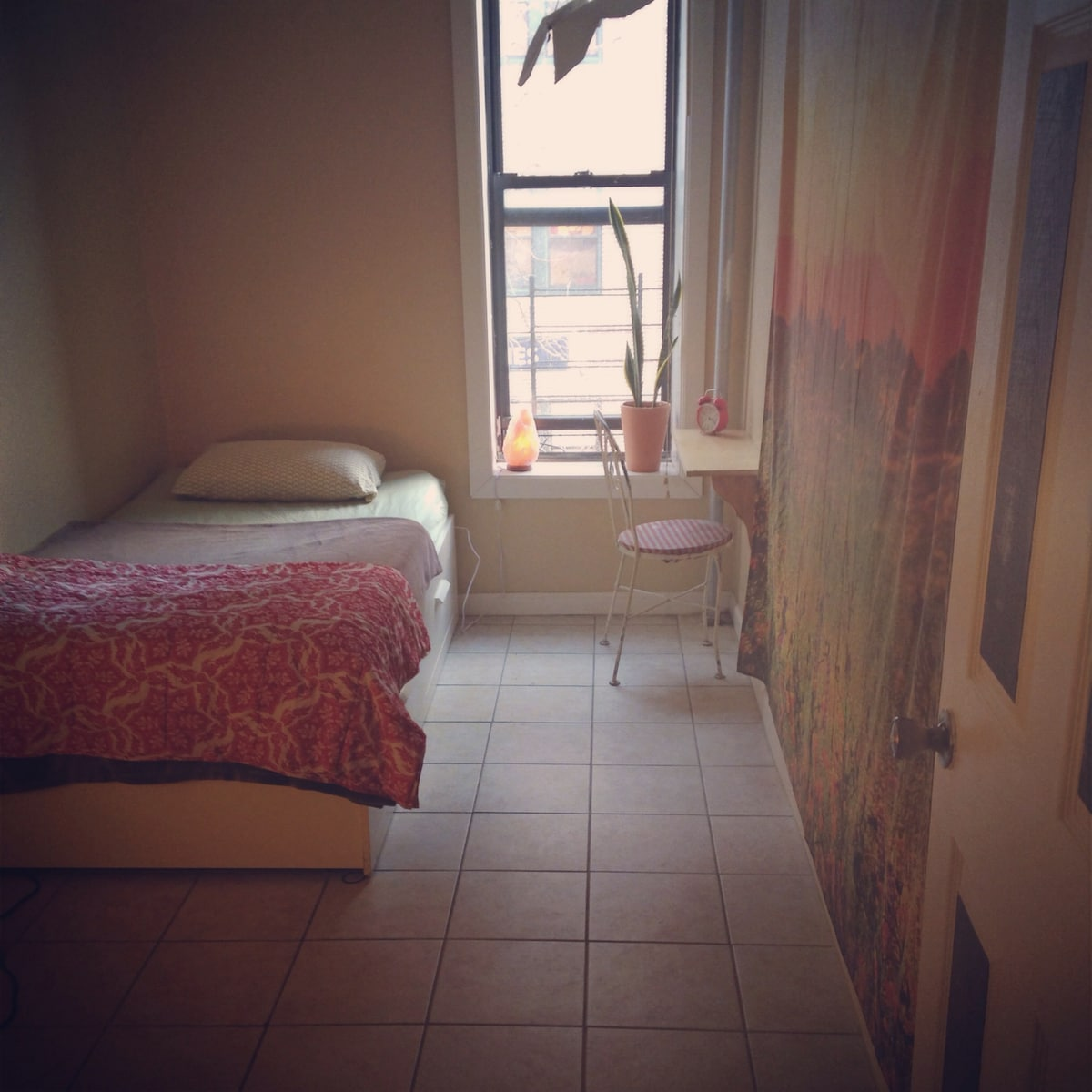 The Scarlet Room has a twin sized bed, small desk and chair, floor lamp, over-the-door clothes rack, and dresser.